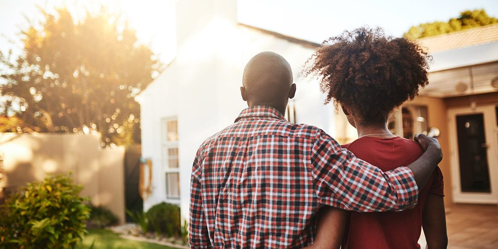 Young couple looking at house.